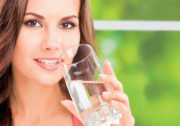 Девушка держит в руке прозрачный стакан с водой