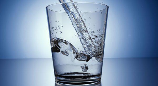 Вода льётся в прозрачный стакан