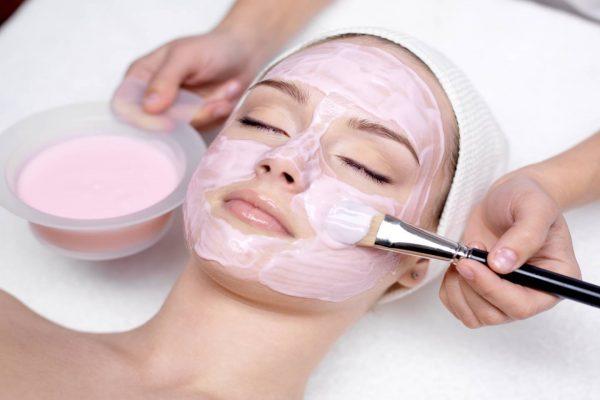 Девушке делают маску из розовой глины