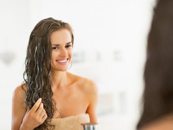 Девушка наносит маску на влажные волосы