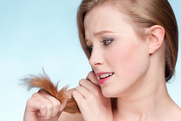 Девушка смотрит на свои ломкие волосы