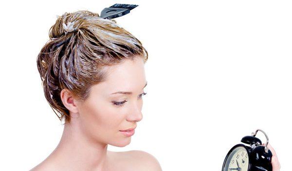 Девушка с маской на волосах смотрит на будильник
