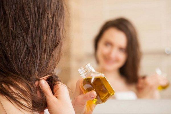 девушка наносит масло на волосы из бутылочки
