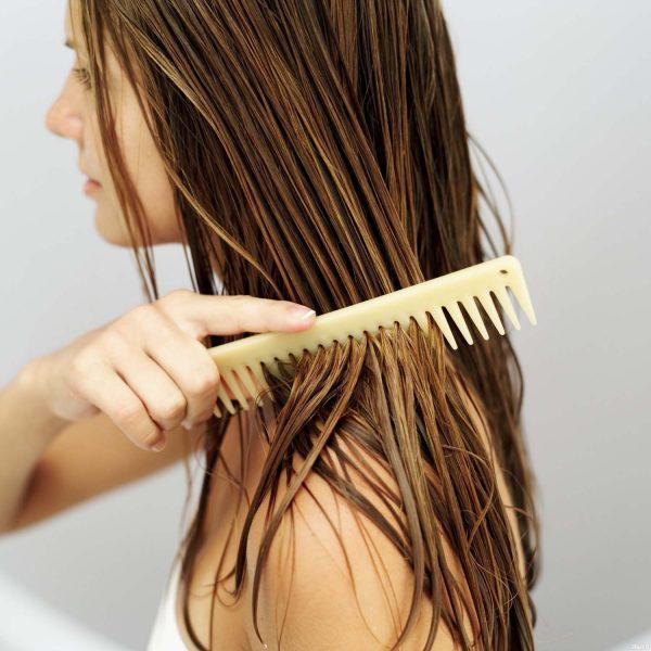 Девушка расчёсывает мокрые волосы