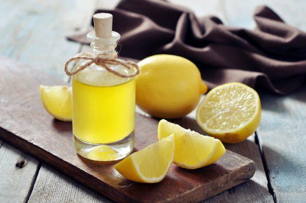 Эфирное масло лимона в бутылочке рядом с лимонами