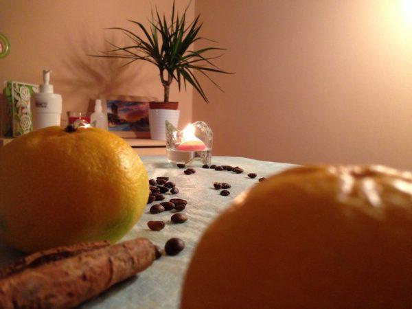 Ароматизированная свеча и апельсины на столе