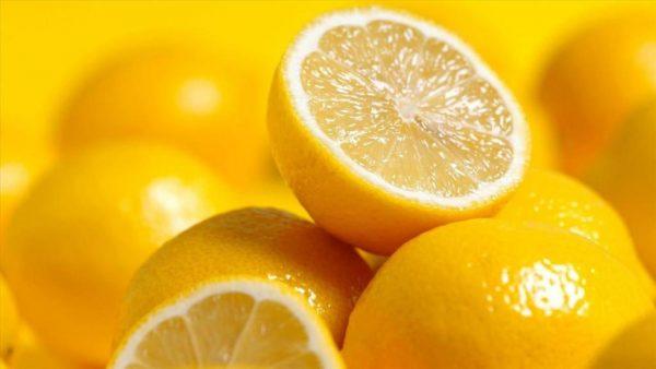 Разрезанный лимон лежит на целых лимонах