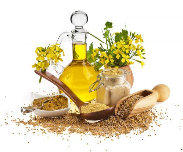 Льняное масло в графине, целые и молотые семены льня, жёлтые цветы в вазе