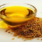 Льняное масло в миске и льняное семя на столе