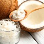 Масло кокоса в стеклянной баночке, целый и расколотый кокосы на столе