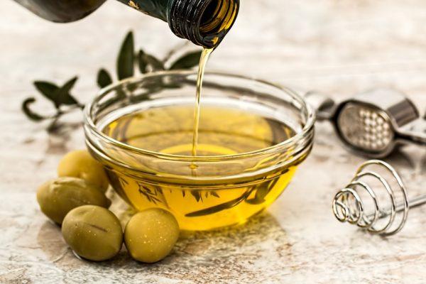 Масло оливы льётся из бутылки в прозрачную миску, рядом лежат целые оливки