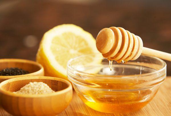 Мёд в прозрачной пиале стоит на столе, позади него лимон, рядом миски с тмином