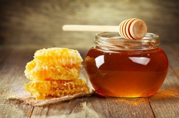 Мёд в стеклянной баночке и мёд в сотах на столе
