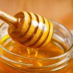 Мёд в стеклянной банке и на специальной ложке для мёда