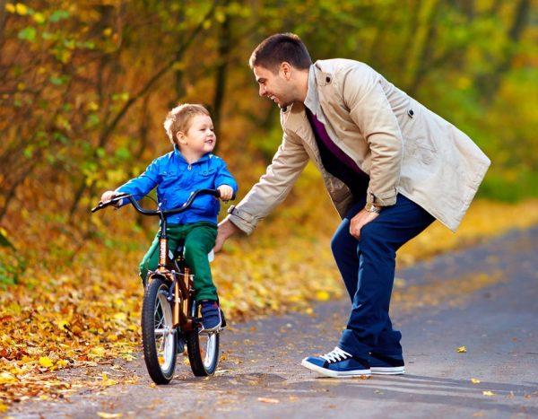 Мужчина и ребёнок на велосипеде в парке