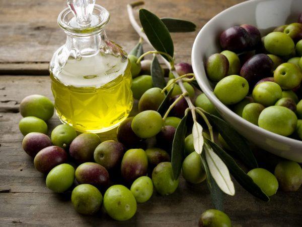 Оливковое масло в прозрачном графине стоит на столе, рядом рассыпаны ягоды оливы и стоит миска с ними