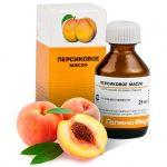 Персиковое масло в бутылочки и три персика