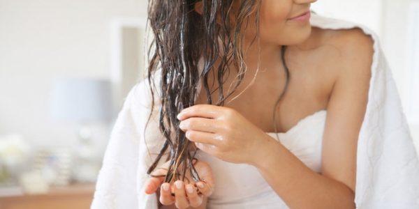 Девушка наносит масло на влажные волос