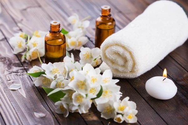 Полотенце, цветы жасмина и эфирное масло в бутылочках