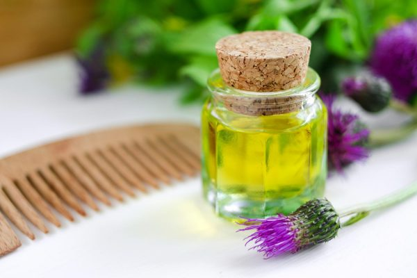 Репейное масло и цветок репейника на столе