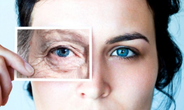 Девушка, держащая фото с изображением морщин вокруг глаз
