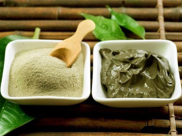 Сухая и пастообразная зелёная глина в двух мисках на бамбуковой подставке