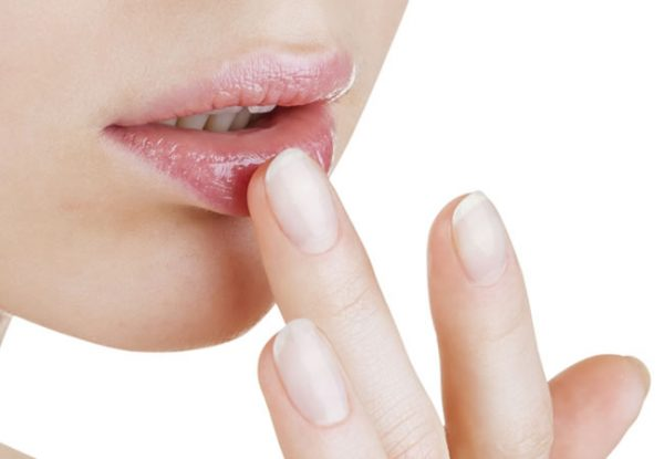 Девушка наносит масло на губы