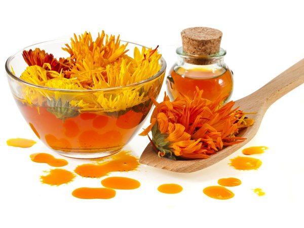 Цветки календулы, масло во флаконе и капли средства на поверхности