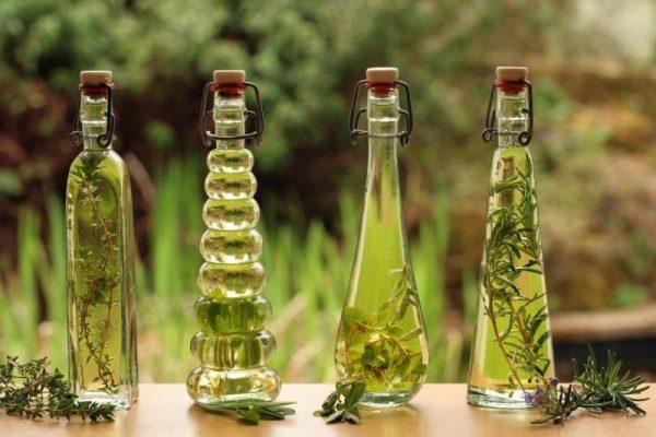 Эфирные масла в длинных стеклянных бутылочках на столе на фоне природы