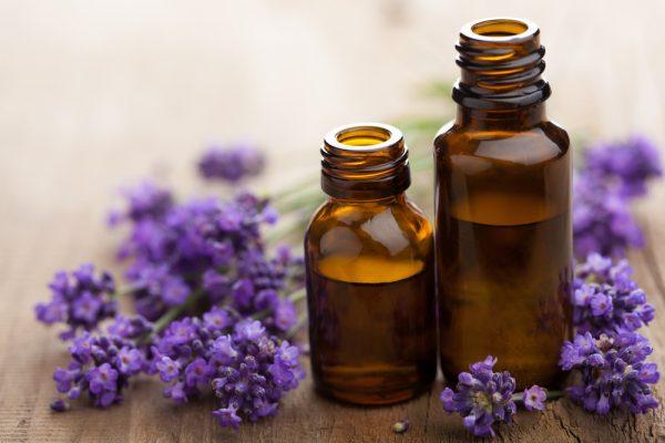 Эфирное масло в темных бутыльках и цветы лаванды на деревянном столе