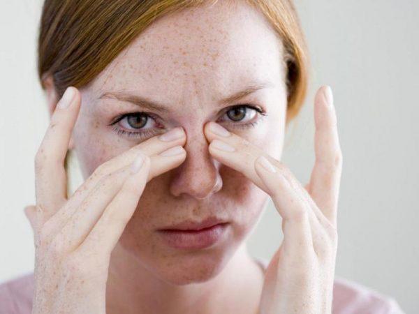 Девушка приложила пальцы рук к основанию носа
