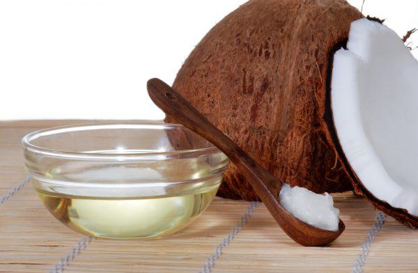 Кокосовое масло в прозрачной пиале и в деревянной ложке