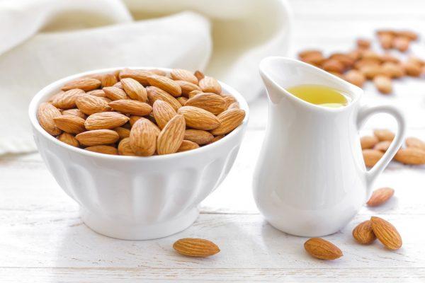 Миндальное масло в белом кувшинчике и одноимённые орехи в пиале