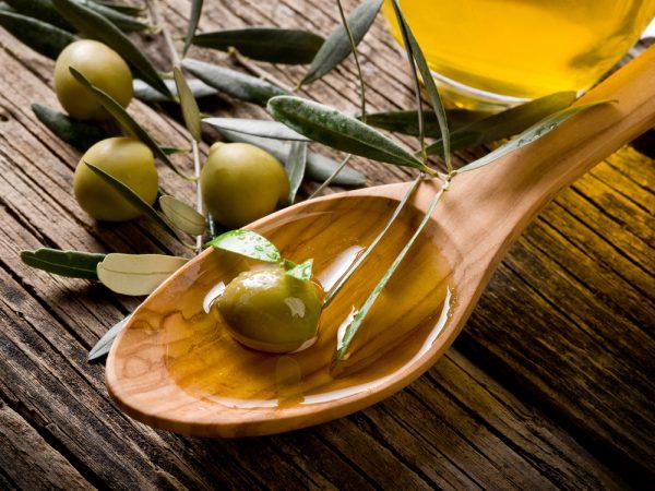 Оливковое масло в деревянной ложке и свежие плоды на столе