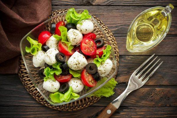 Салат и оливковое масло в соуснице